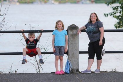 mom, son, daughter on fence with river behind