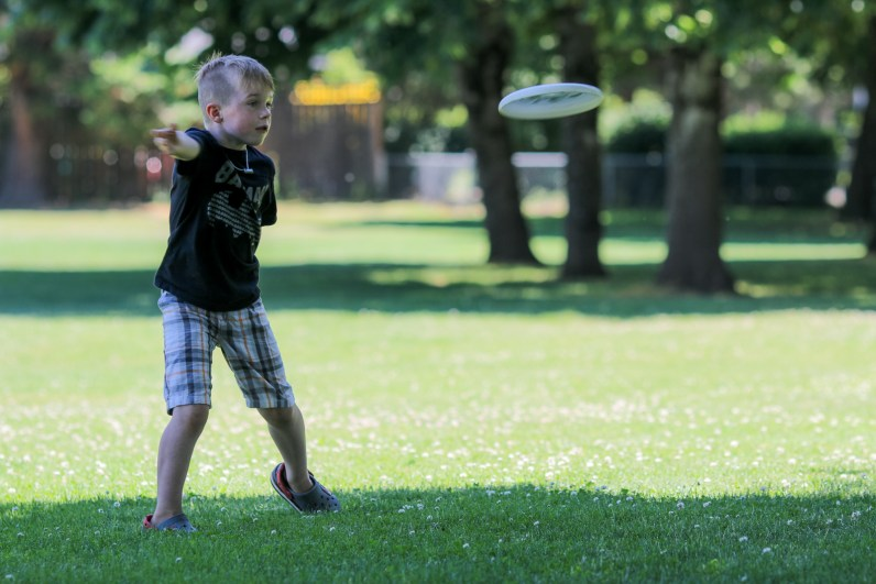 little boy throwing frisbee