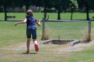 little girl throwing horseshoe