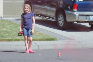 little girl standing by smoke bomb