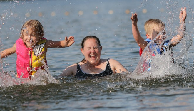 mom and kids splashing in the lake