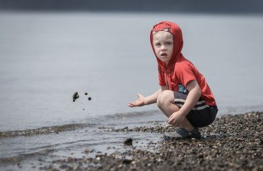 evan throwing sand into puget sound