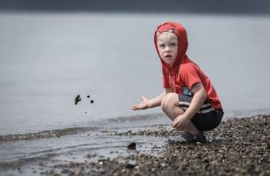 evan throwing sand into puget sound