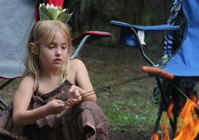 little girl cooking hot dog over fire