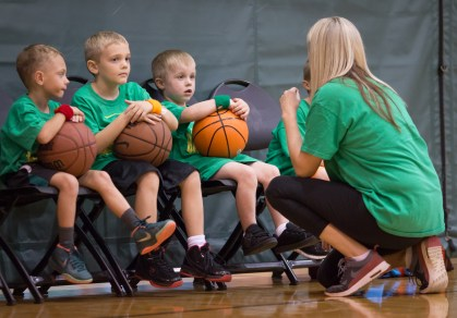 coach talking to kids' basketball team