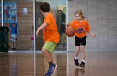 little girl dribbling basketball