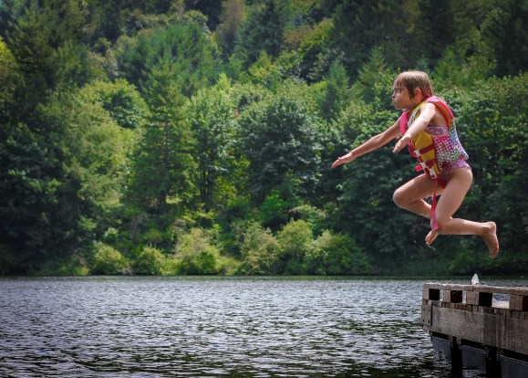 little girl jumping off dock into lake