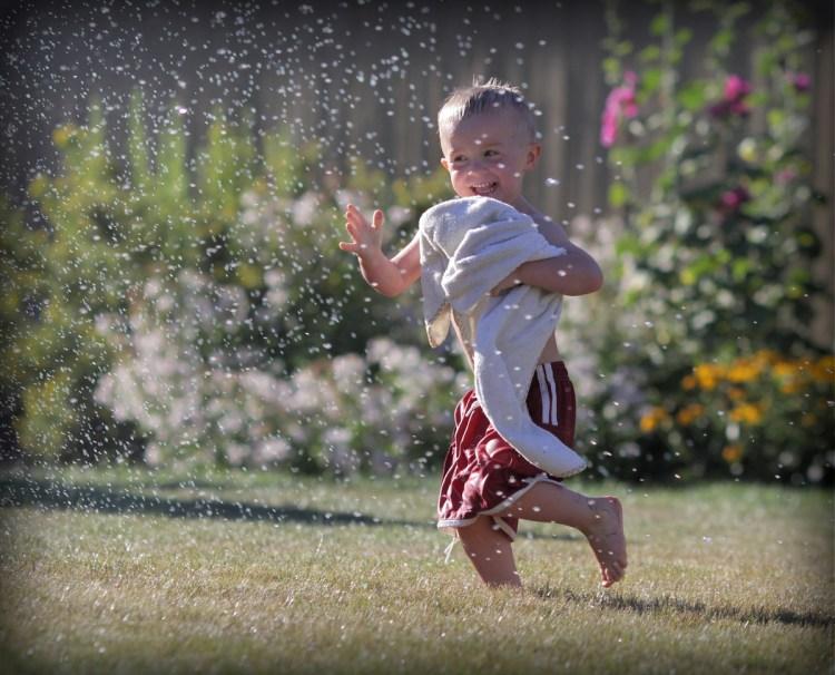 little boy running through sprinkler in back yard