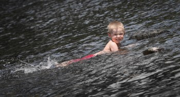 kid on tummy in river