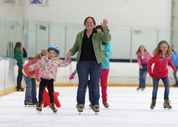 mom with daughter waving ice skating