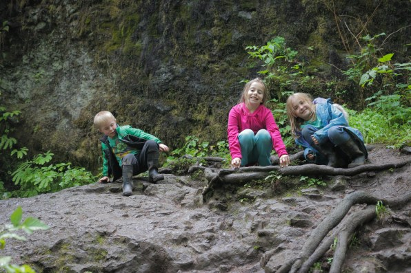 kids climbing on rocks in woods