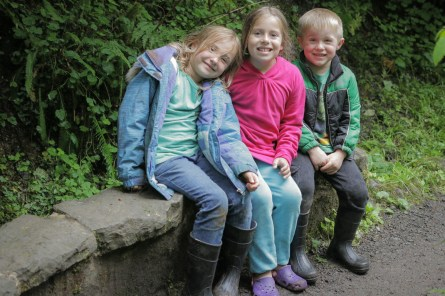 three kids sitting in woods