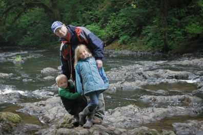 daddy daughter son on rocks in river