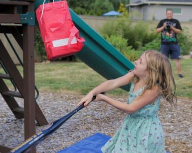 little girl hitting pinata with bat