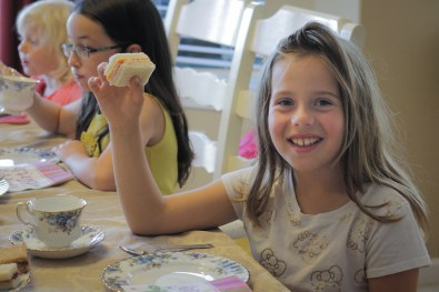 girl eating sandwich at birthday party