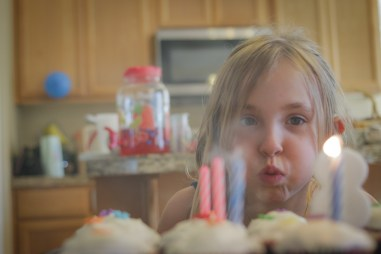little girl blowing out candles on a birthday cake