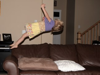little girl jumps backward off couch