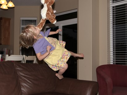 little girl airborne jump off couch