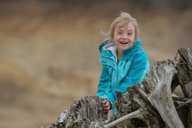 smiling girl on log at beach
