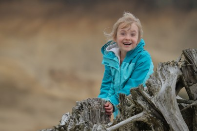 smiling girl on log at beach