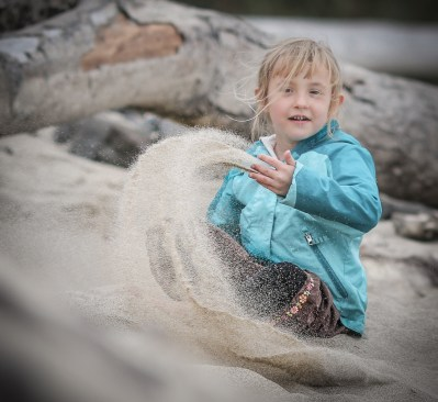 little girl throwing sand - looks magical