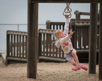 little girl doing monkey bars