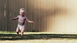 kid running around in diaper in back yard