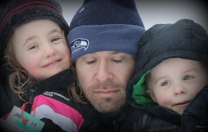 dad in seahawk beanie with two kids