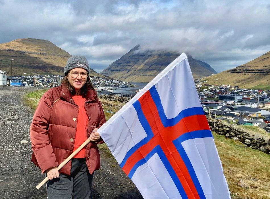 Kinga z farerską flagą. W tle panorama Klaksvík.