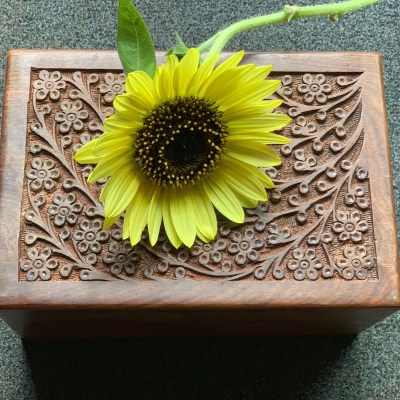 Dog cremation ashes in wooden box with sunflower