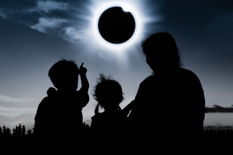 Kids and parent watching solar eclipse.
