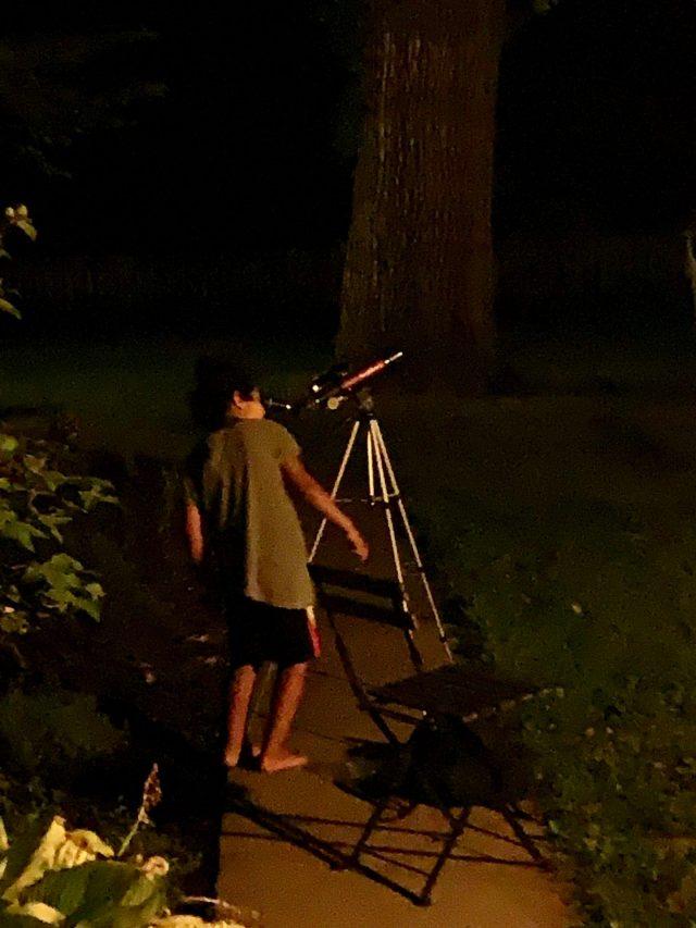 Kid looking through telescope at stars.
