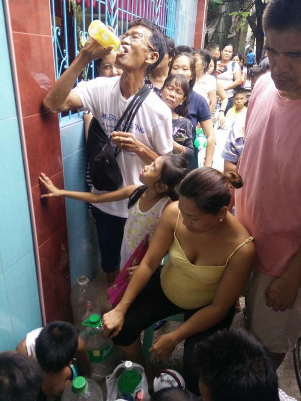 CAUTION. Residents lineup to drink water that began dripping from a crack in the San Roque Parish in Basak-Pardo. (Photo from DYLA Facebook page)