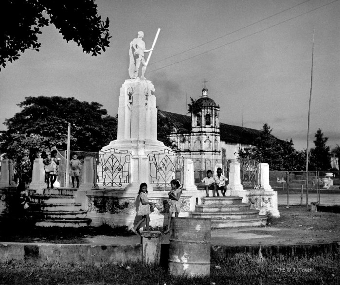 """LAPULAPU. A photograph of the Lapulapu stature on October 10, 1949 by """"Life"""" photographer Jack Birns. Beyond the statue is the old Opon church. (Photo from John Tewell's Flickr account)"""