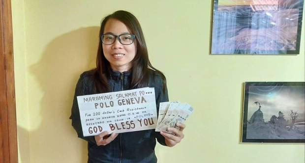 CASH ASSITANCE. An overseas worker shows the cash assistance she received from the Philippine government. (Photo from the Department of Labor and Employment Facebook page.)