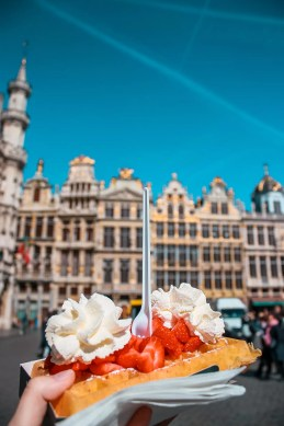 Belgian Waffle in front of Brussels Grand place Perfect 2 day Brussels itinerary