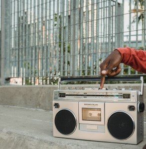 Black man pressing button on retro Cassette recorder sitting on outdoors in in the city