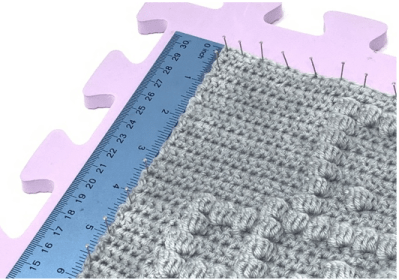 Image of crochet square being pinned into shape