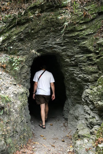 man walking into dark cave