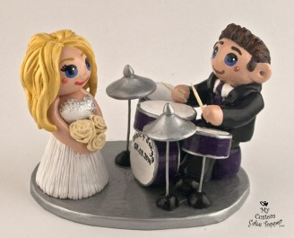 Groom playing the drums for his bride cake topper