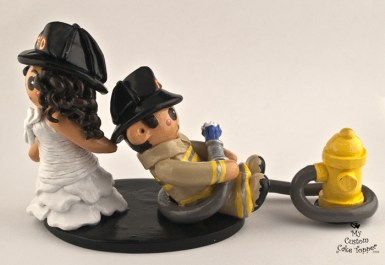 Fireman bride dragging her fireman groom cake topper