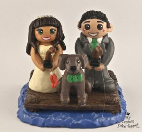 Bride and groom fishing off a dock with dog cake topper