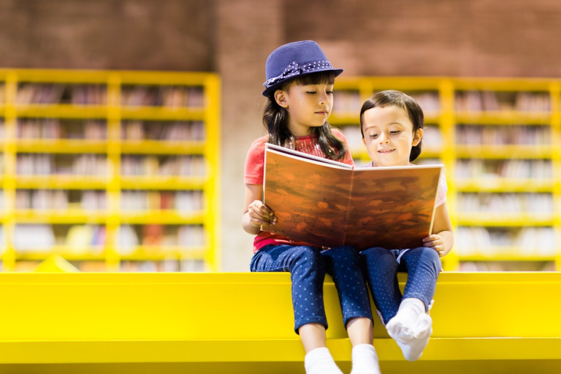 two children reading and sharing