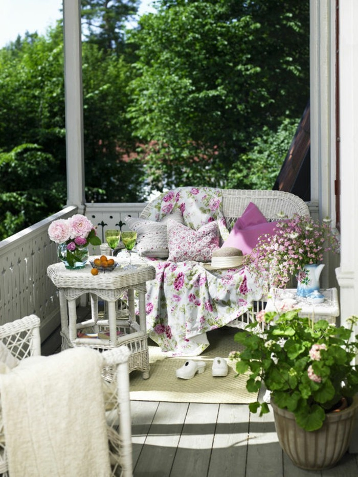 White wicker furniture and geranium on balcony