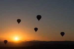 上空に浮かぶ数基の気球 夜明け