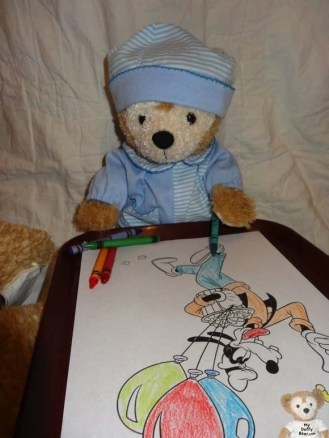 Duffy the Disney Bear colors a picture of Goofy eating Popcorn