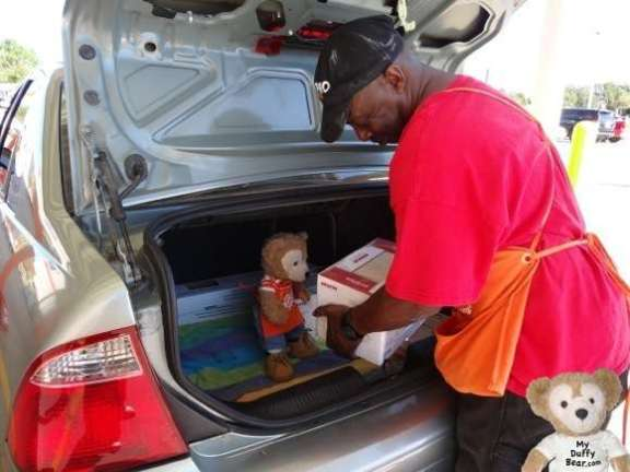Duffy the Disney Bear helps pack car trunk at the Home Depot