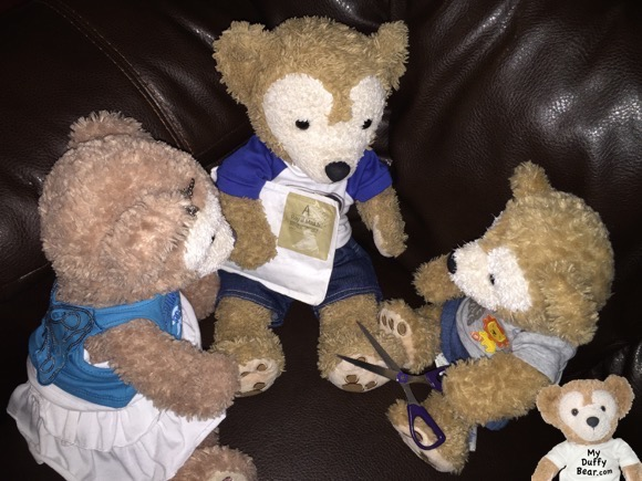 Duffy the Disney Bear shows the package with his Teddy Bear Olympics Medal to ShellieMay and Little Joe
