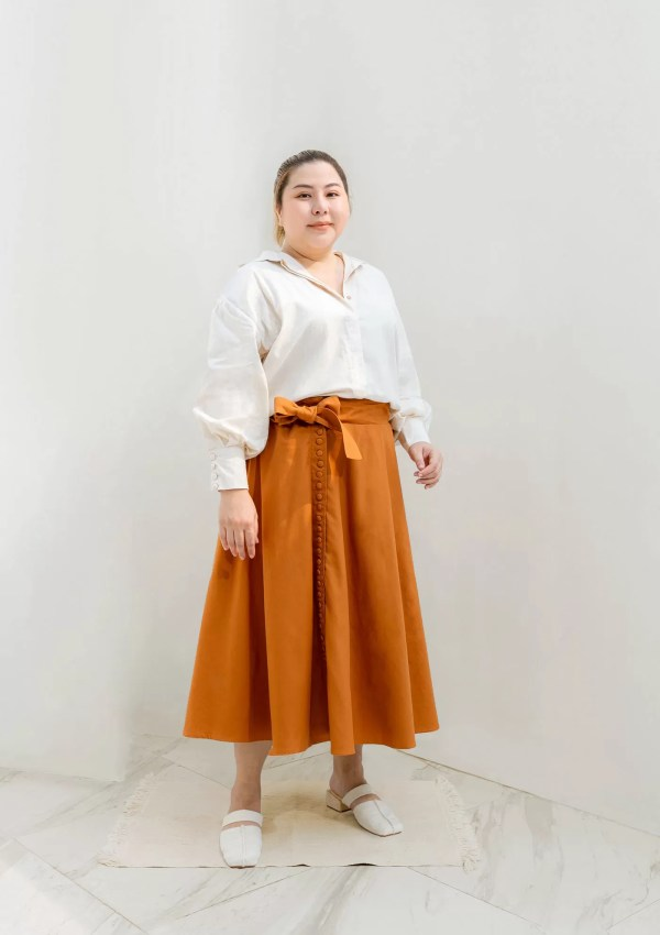 Plus size woman wearing orange cotton skirt and shirt from sustainable cotton