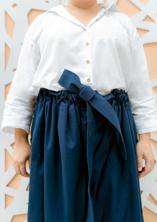 Plus size woman wearing dark blue cotton trousers and white shirt